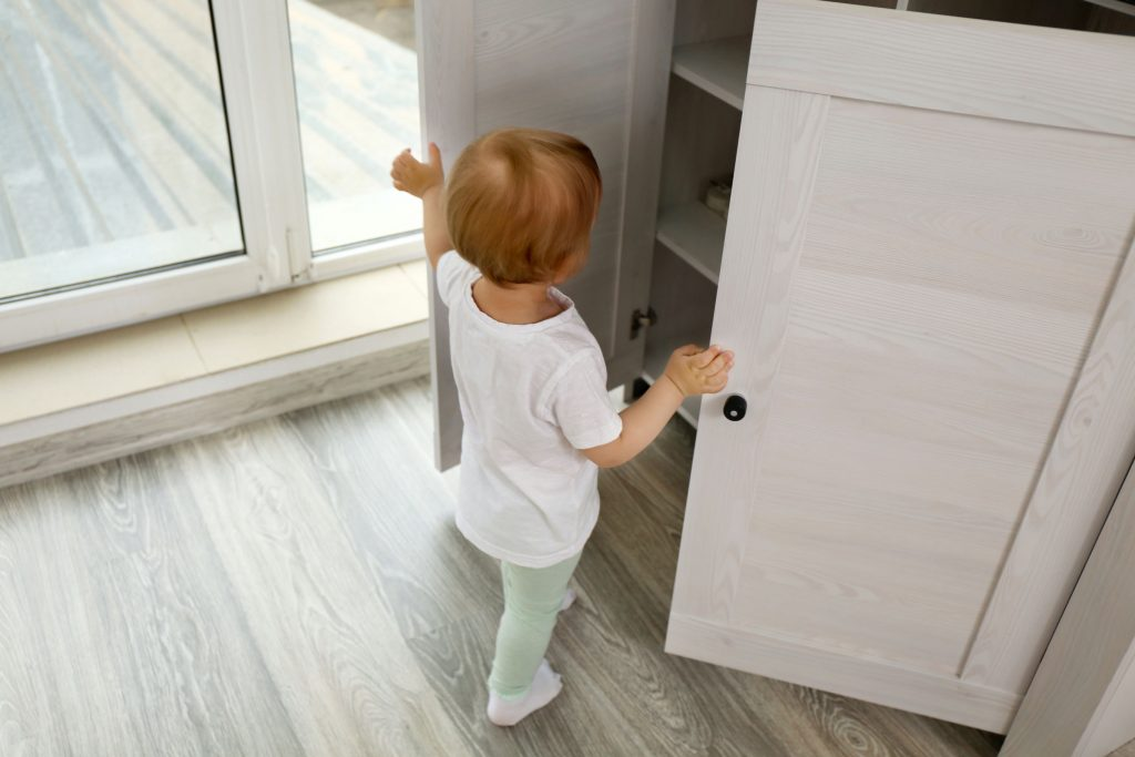 Cute baby girl playing with a wooden cupboard